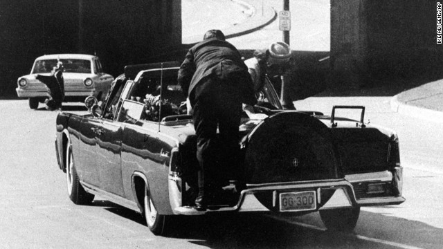 Clint Hill climbs on the trunk of the Presidential limo